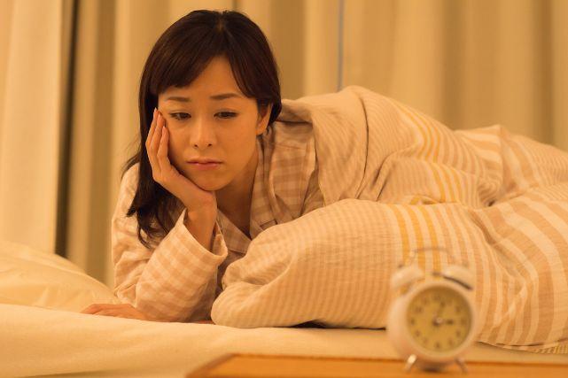 眠れなくて時計を見つめる女性